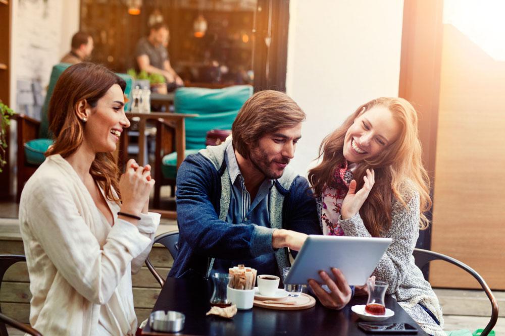 Ein Mann und zwei Frauen mit Tablet