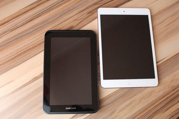Schwarzes Tablet von Samsung und weißes Apple-Tablet auf hölzerner Unterlage