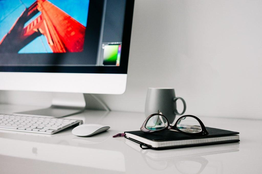 iMac mit Notizblock, Brille und Cup