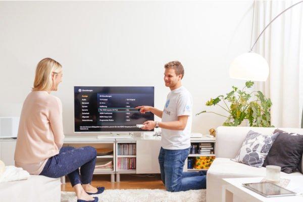 Techniker erklärt der Kundin den Fernseher