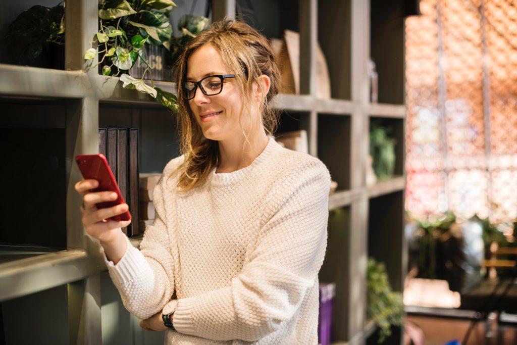 Frau mit Smartphone vor Bücherregal
