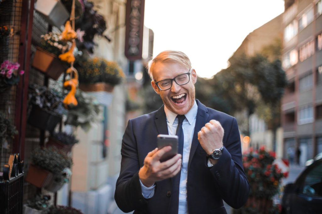 Mann mit Smartphone in Siegesposition